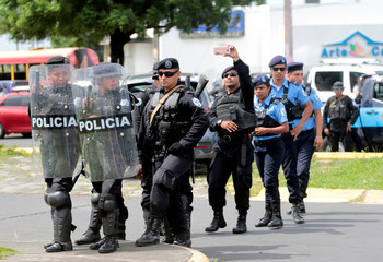 A riot police uses his cell phone to takes pictures to demonstrators during a protest against Nicaraguan President Daniel Ortega's Government in Managua