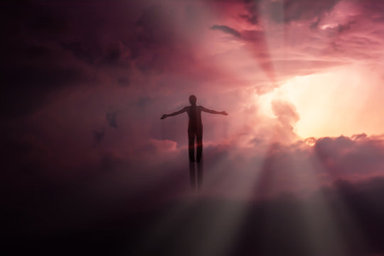 Silhouette of a man flying up in the sky in the bright rays of the sun with arms spread apart.