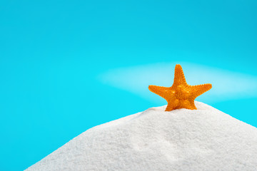 orange color starfish on white sand on blue background concept of summer vacations
