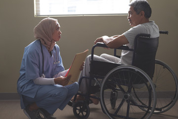 Female patient interacting with disabled male patient in the ward