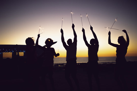 Friends playing with sparklers on the beach at dusk