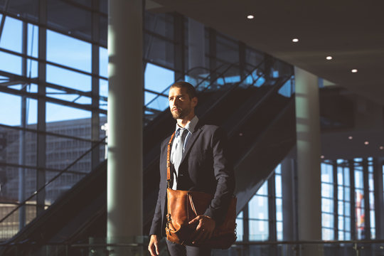 Businessman with office bag looking away in a modern office building