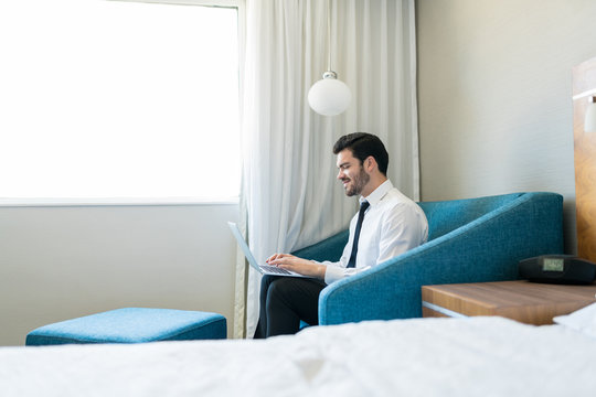Executive Working On Laptop In Hotel Room
