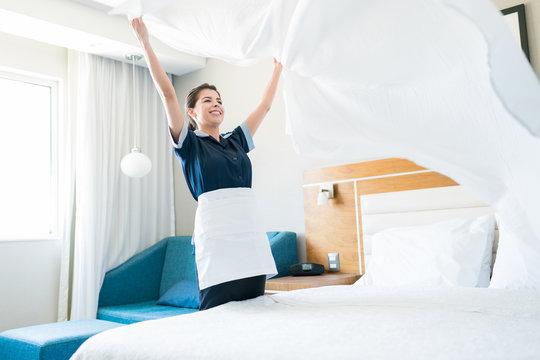 Female Housekeeper Making Bed In Hotel