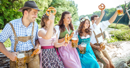 Five friends, men and women, having fun on Bavarian RIver and clinking glasses with beer