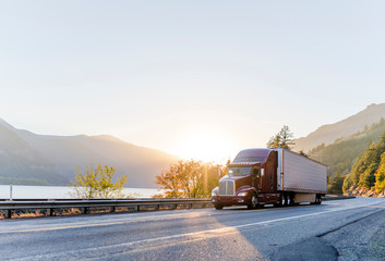 Big rig burgundy semi truck transporting commercial cargo in refrigerator semi trailer driving on the road along Columbia River with sunshine Wall mural