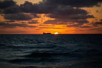 Silhouette of a fishing ship in the sea at early morning with the sun coming up in a summer sunny day, Florida, USA. Sunsert at South Beach, Miami.