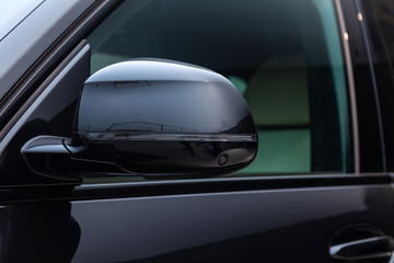 Black new car year side mirror with 3d camera view with lifht gray interior on parking in the street
