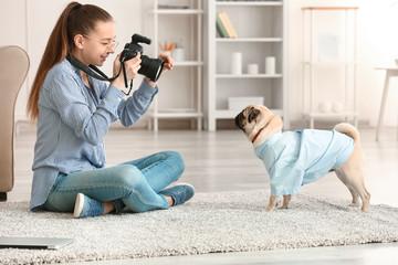 Teenage girl taking photo of her cute dog at home