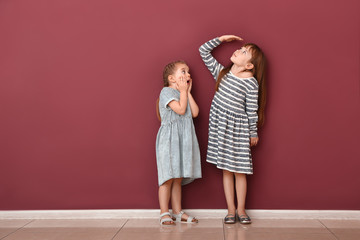 Little girls measuring height near wall Wall mural
