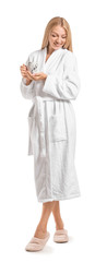 Wall Mural - Beautiful young woman in bathrobe drinking coffee on white background