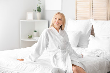 Wall Mural - Beautiful young woman in bathrobe sitting on bed
