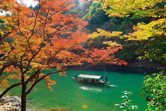 beautiful scene with tourist boat and Hozugawa river in Arashiyama park in autumn season, Kyoto, Japan