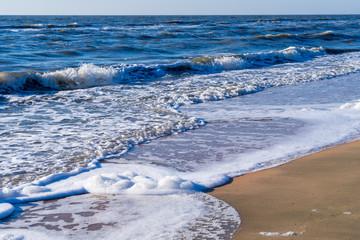 Image of sea foam on a sandy beach.