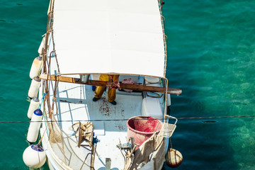 The fisherman working on white fishing boat  and fish in the mediterranean sea port