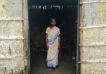 Madhubala Mandal poses for a photograph inside her bamboo hut in Bishnupur village