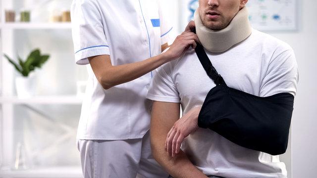 Female surgeon adjusting male patient arm sling, orthopedics and rehab period