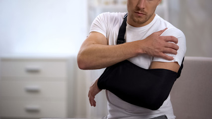 Male in arm sling suffering pain in shoulder, result of work trauma, orthopedics Wall mural