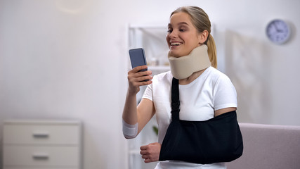 Cheerful woman in foam cervical collar and arm sling chatting on cellphone rehab Fotobehang