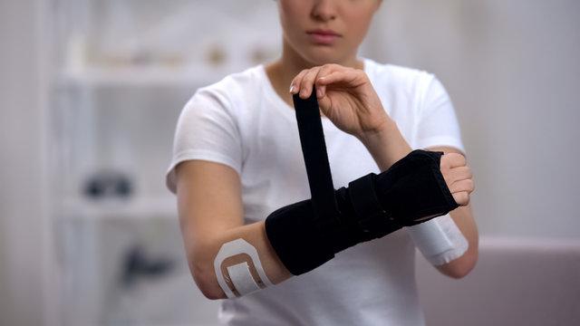 Young sportswoman applying titan wrist brace rehabilitation after trauma, health