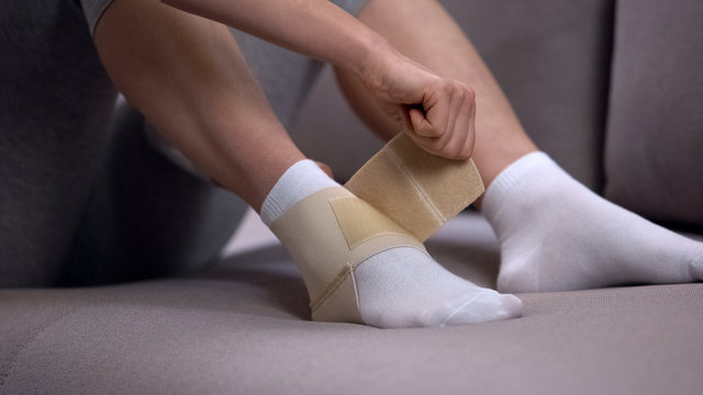 Woman fixing two-strap ankle wrap in proper position, sprained joint, healthcare