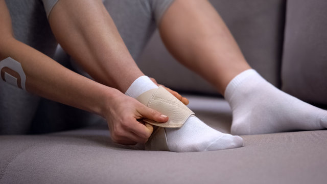 Lady fixing two-strap ankle wrap in proper position anti-inflammatory medication