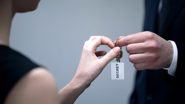 Male giving woman keys to Secret information, security clearance, data leakage