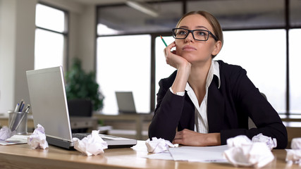 Bored woman thinking over startup in office, lacking new ideas, unmotivated