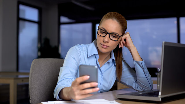 Lazy woman using phone instead of doing job on computer, unproductivity concept