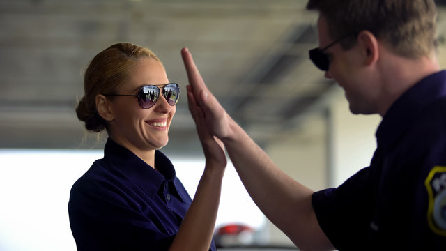 Smiling police teammates giving high-five to each other, coworking concept, team