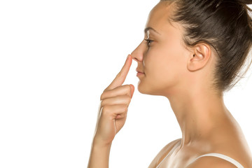 young woman touches her nose with her finger on a white background