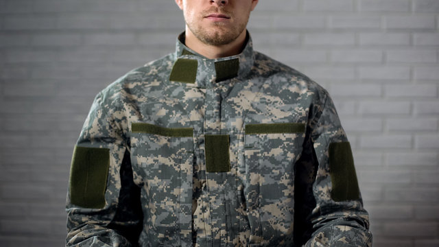 Soldier in camouflage sitting against white wall, military service, template