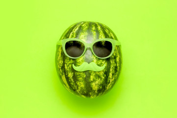 Summer funny watermelon in green glasses and with green mustache on bright green background top view flat lay. Minimal fruit concept. Creative product idea, summer festival, summer background