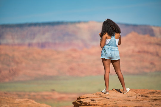 African girl standing on the top of a rock enjoying the canyon, back view