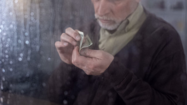 Poor retired man counting money in hand, economic crisis, financial problem