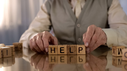 Senior man making word help of wooden cubes on table, parkinson disease, tremor Wall mural