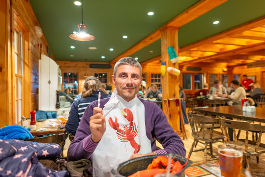 Man enjoying eating Lobster in Maine
