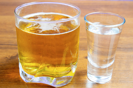 Vodka and beer in different glasses on a wooden table