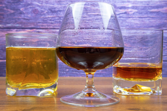 Three glasses with different colored alcoholic drinks
