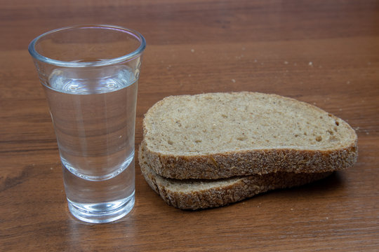 A glass of vodka and sliced black bread on a wooden table