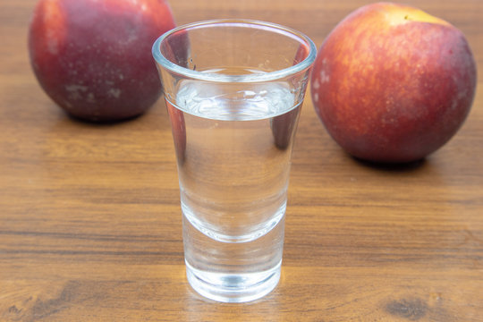 Transparent peach liqueur in a glass and two peaches on a wooden table