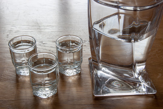 Three glasses of vodka and a decanter on a wooden table