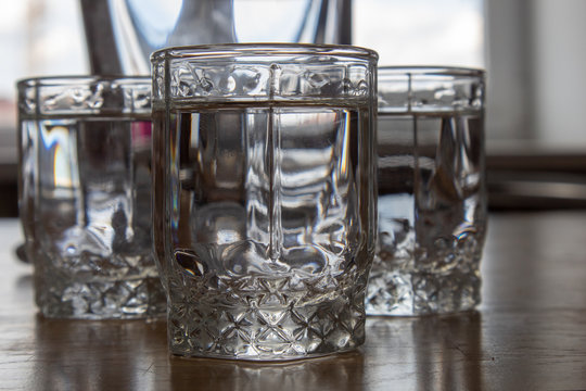 Three glasses of vodka on a wooden table