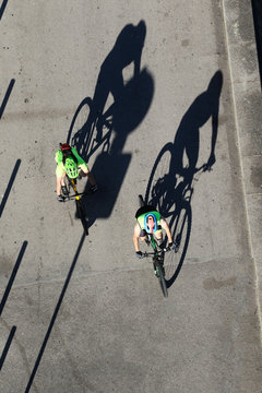 Top view of two cyclists on the road with shadows