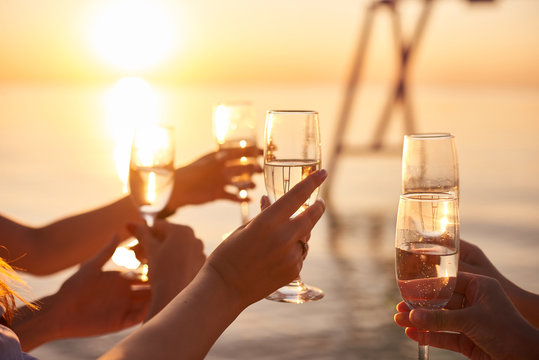 Happy young women drinking champagne at bachelorette party on the beach. Bride and bridesmaid having fun at hen party