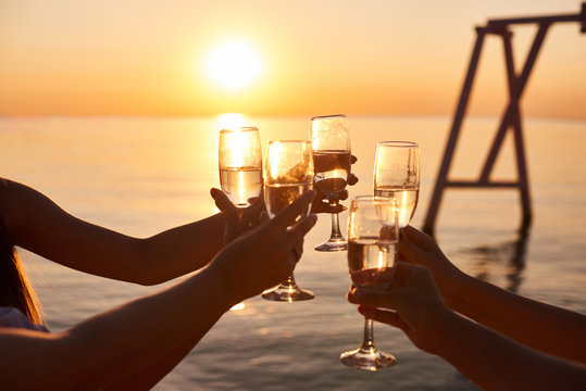 hen party before the wedding. girls relax at the resort. early morning friends drink champagne and meet the dawn on the ocean