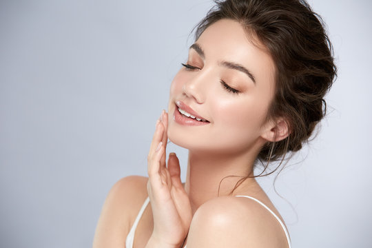young and happy girl with light make-up and closed eyes touching her chin and smiling