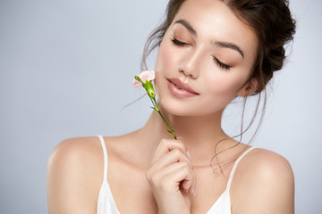 cute girl with perfect skin and white flower near face closed eyes