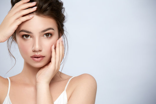 young and fresh model touching her face with arms and looking to camera