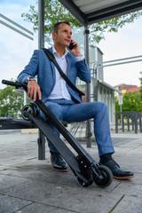 Mann wartet mit e-scooter an haltestelle und telefoniert